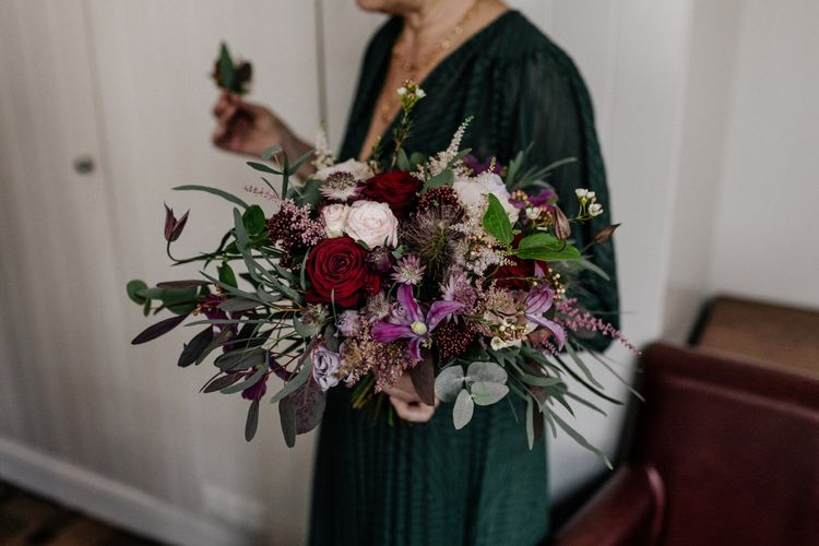 Red, pink and purple wedding bouquet with foliage