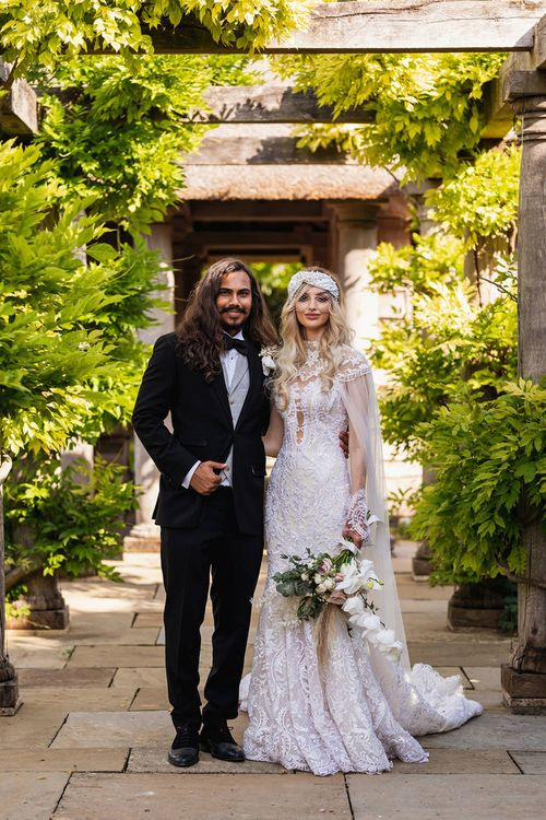 Stylish bride and groom in black suit and Wona Concept wedding dress at The Lost Orangery