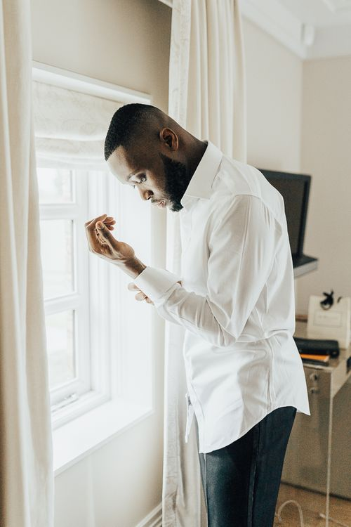 Groom buttoning the cuffs on his shirt whilst getting ready
