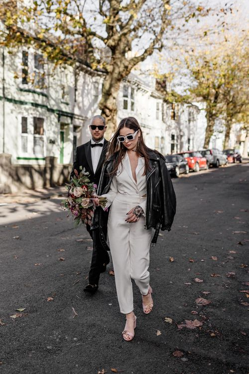 Alternative bride and groom walking through the Brighton streets at stylish micro wedding