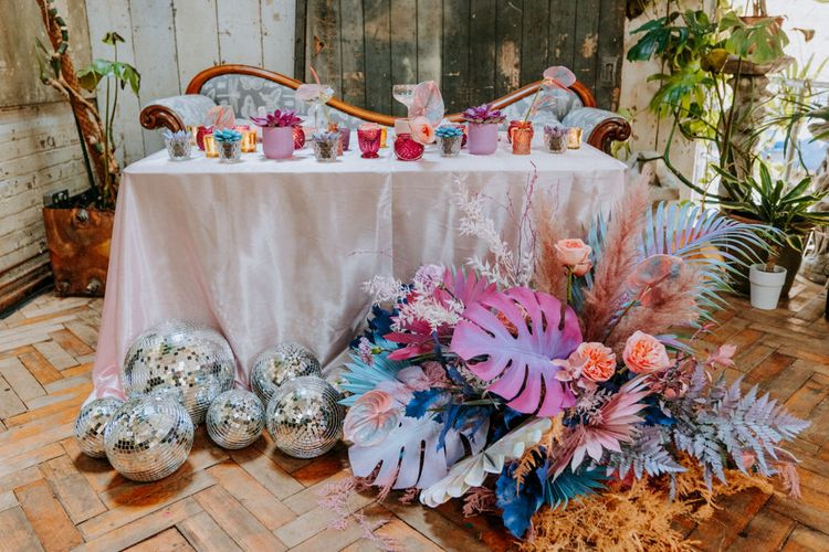 Sweetheart table at festival wedding with holographic pastel wedding decor and flowers
