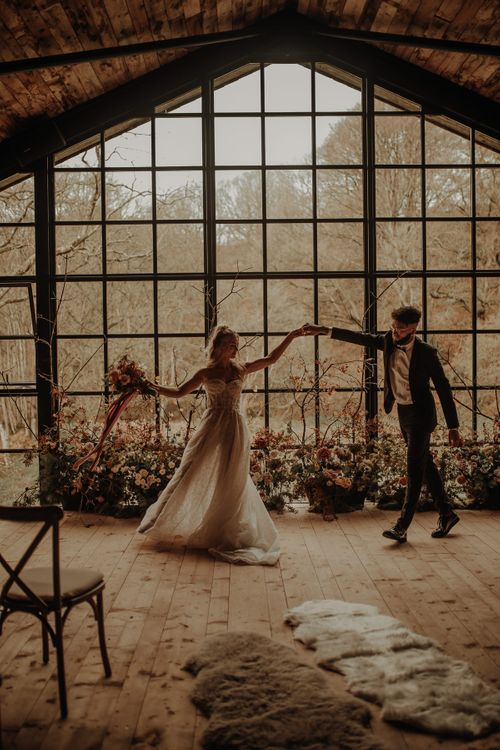Bride and groom dancing in front of the crittal windows at The Hidden River Cabins