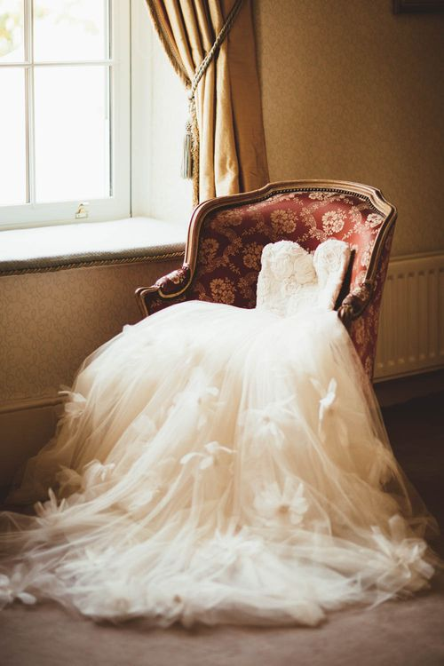 Wedding dress sprawled on a chair on the morning of the wedding