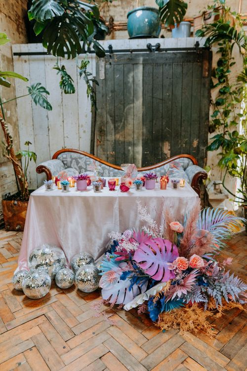 Colourful sweetheart table with iridescent flowers, disco balls and votives.
