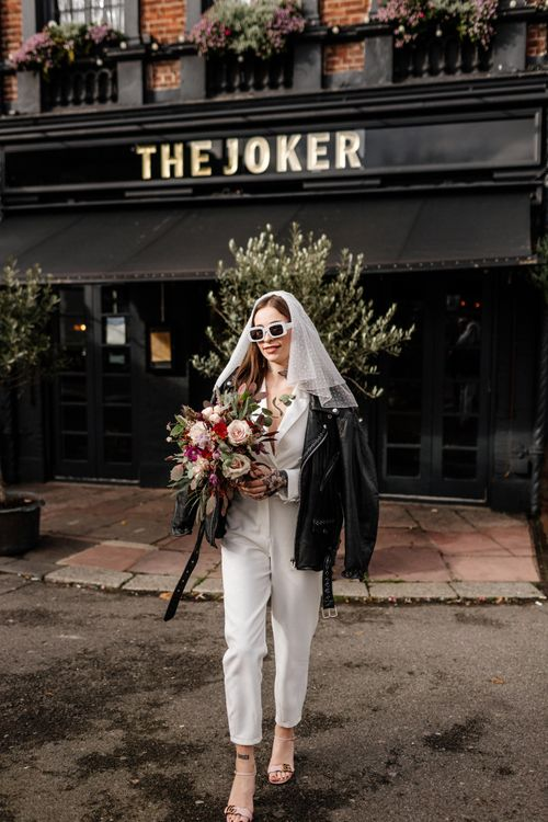 Stylish bride in jumpsuit, polka dot veil and leather jacket