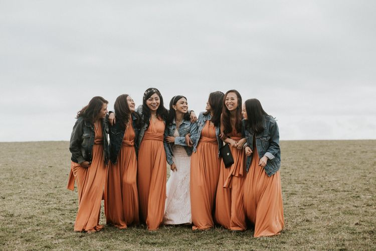Bridesmaids in orange dresses and enim jackets