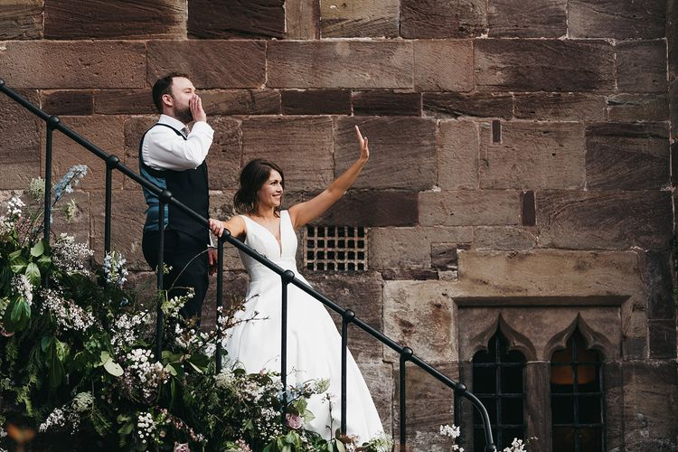 Bride and groom wave at wedding guests