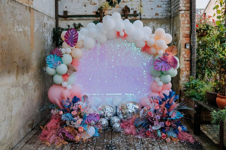 Altar back drop with sequin sheet, balloon installation and glitter balls