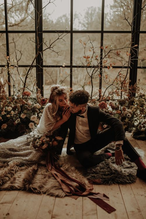 Bride and groom sitting on faux fur rugs