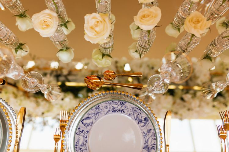 Place setting with blue and white plates gold cutlery and white flowers in vases