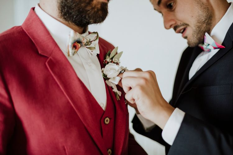 Groom in red suit getting ready for wedding