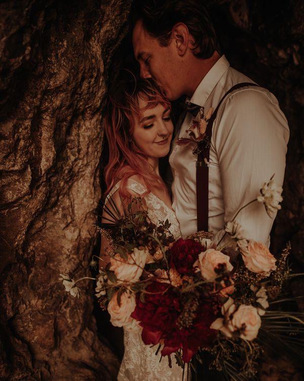Groom kissing his brides head