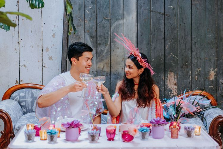 Bride and groom sipping champagne at sweetheart table
