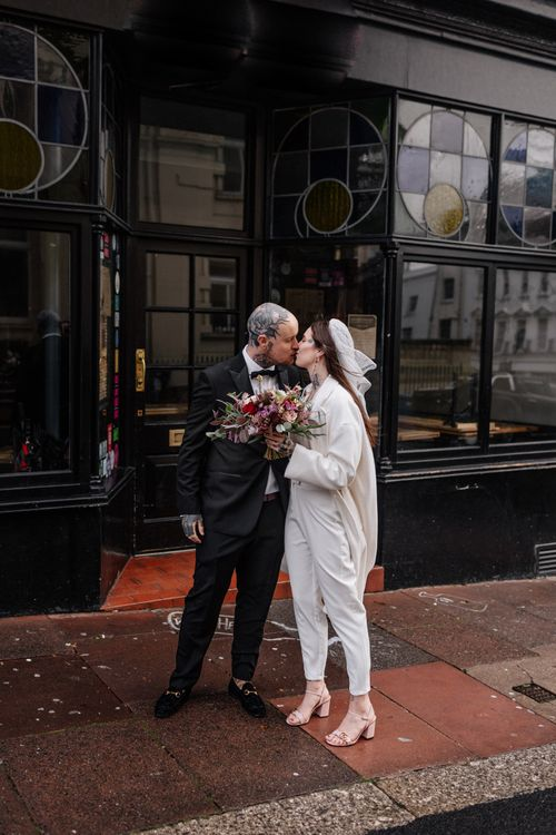 Alternative bride and groom in tuxedo and jumpsuit