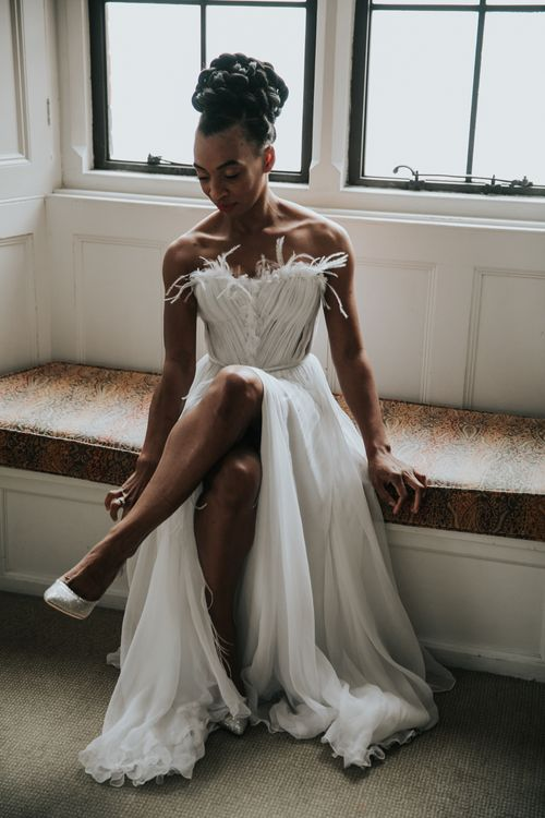 Bride in feathered wedding dress with skirt split