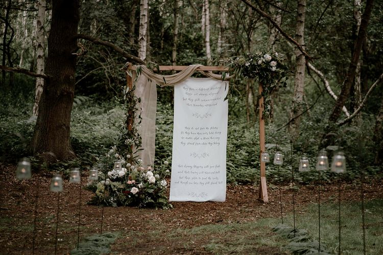 Wooden frame int he woods decorated with drapes, flowers and fabric sign