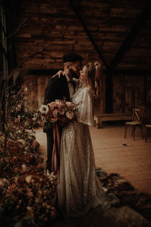 Bride and groom kissing at autumn/winter wedding inspiration shoot