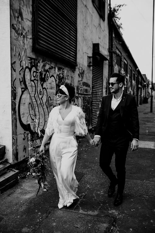 Bride and groom holding hands walking through the Liverpool streets