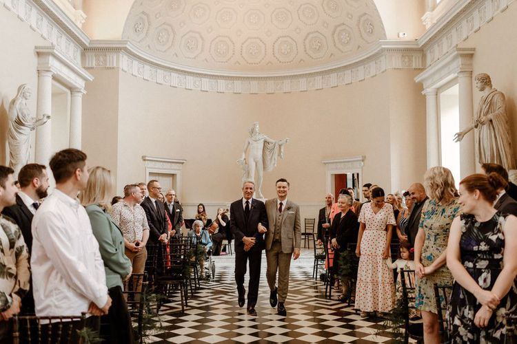 Son being walked down the aisle by his dad at same sex wedding