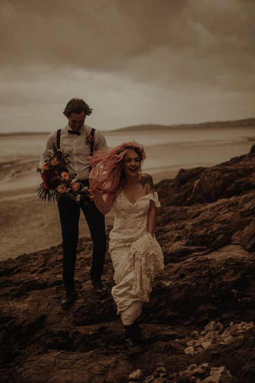 Bride with pink hair blowing in the wind at beach elopement