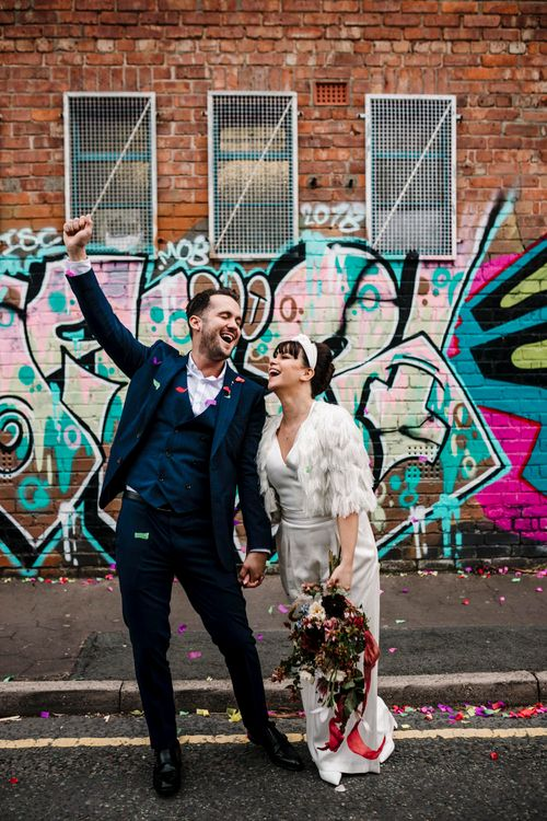 Bride and groom smiling in front of graffiti covered walls