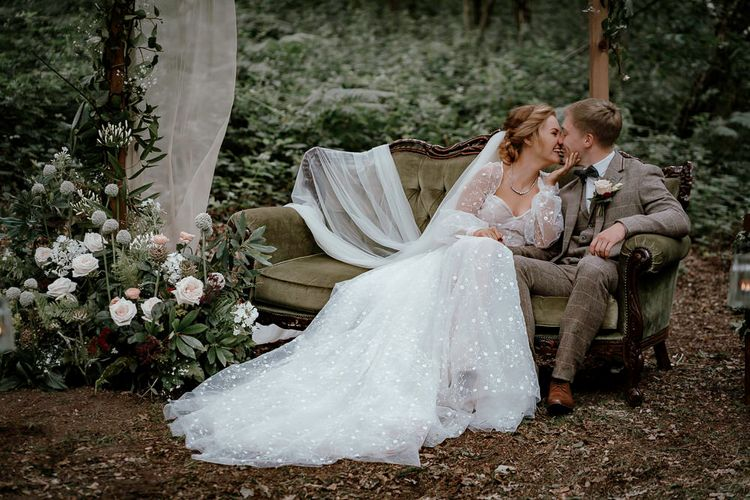 Bride and groom kissing on a vintage couch in the woods