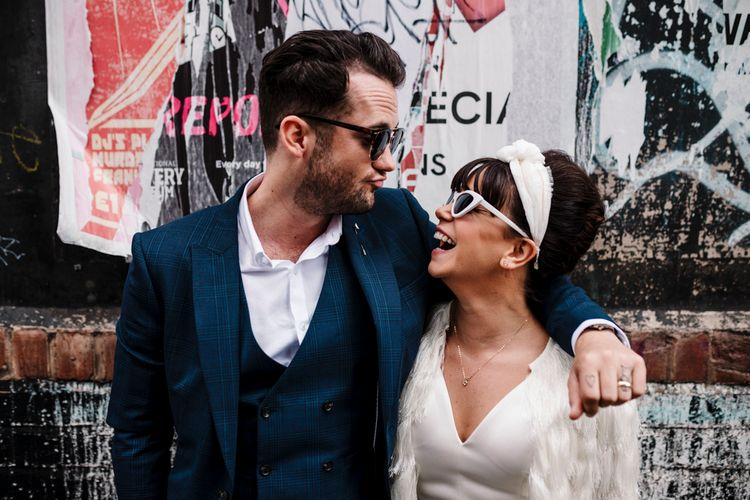 Stylish bride and groom in sunglasses looking at each other