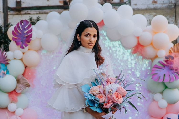 Bride in short wedding dress and boots holding her holographic pastel bouquet