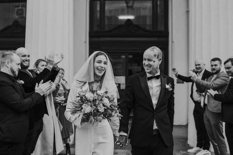 black and white portrait of bride and groom exiting the wedding ceremony