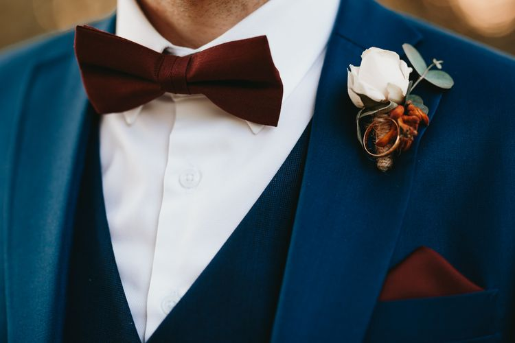 Navy suit and burgundy bow tie