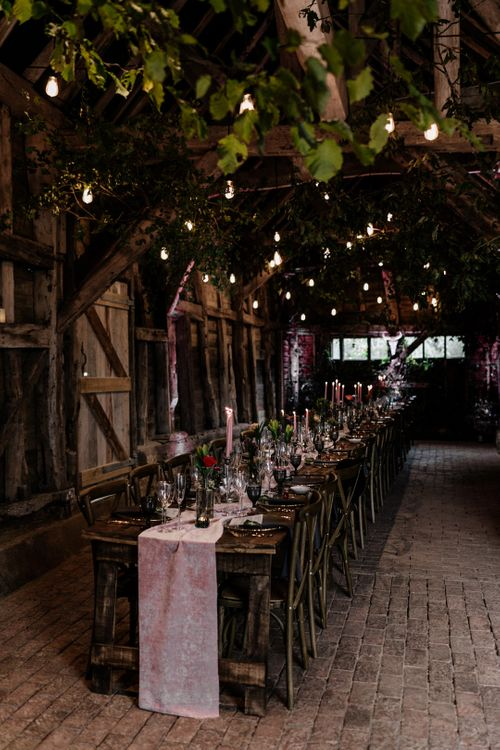 High Billinghurst Farm barn intimate wedding reception with lights and candle decor