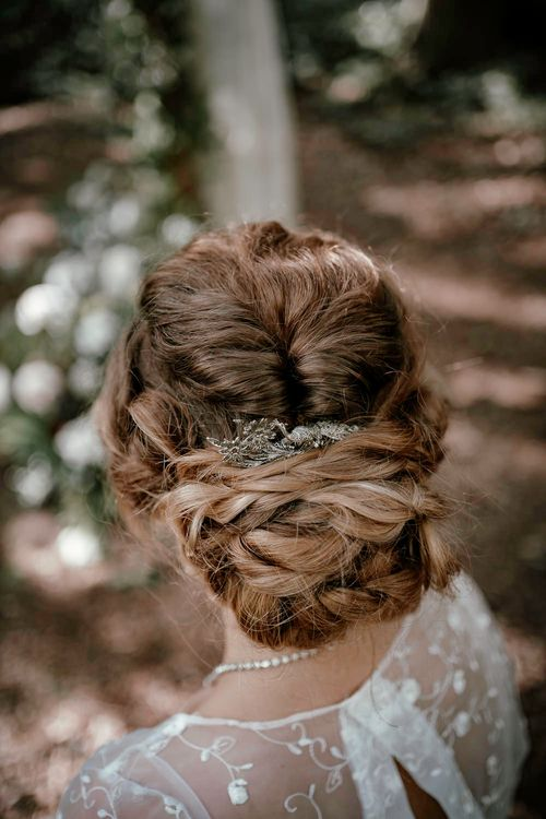 Pinned updo with peacock hair accessory