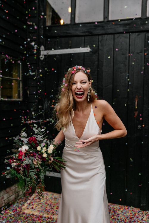 Bride in satin wedding dress covered in confetti at 2020 wedding