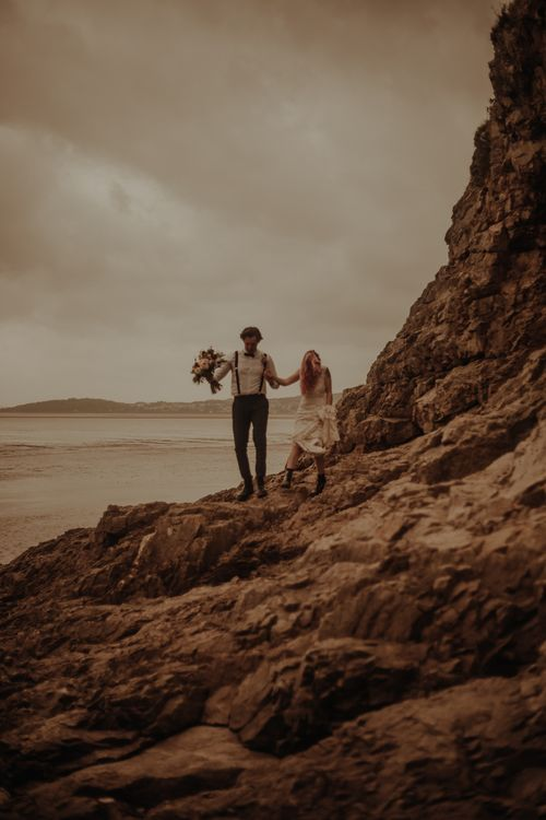Bride and groom walking on the rocks at beachside elopement
