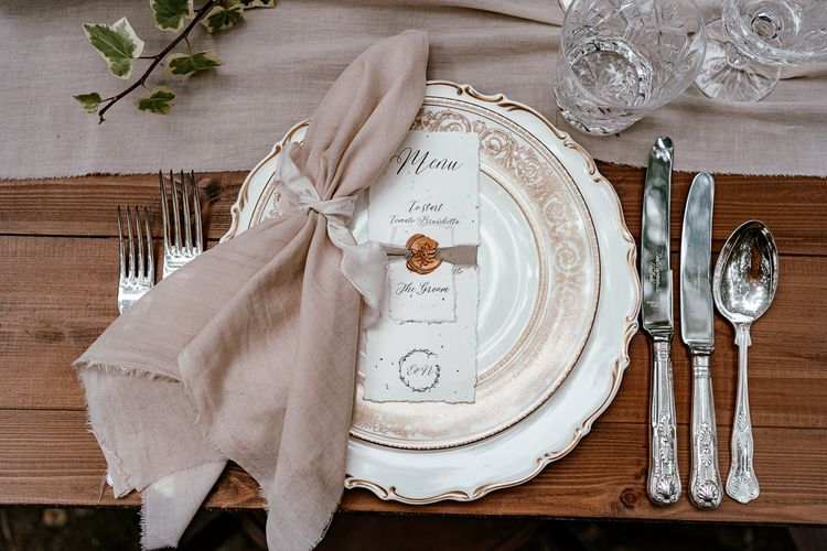 Place setting with vintage plates and cutlery, natural linen napkin and recycled paper menu card