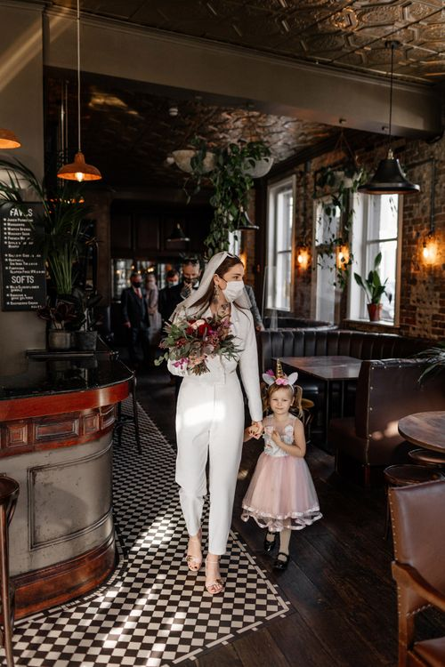 Bride in jumpsuit with flower girl in a pink tutu