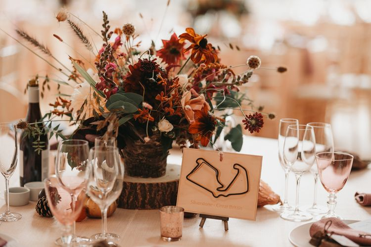 Rustic centrepiece with wooden tree slice and grand prix track table names and signs