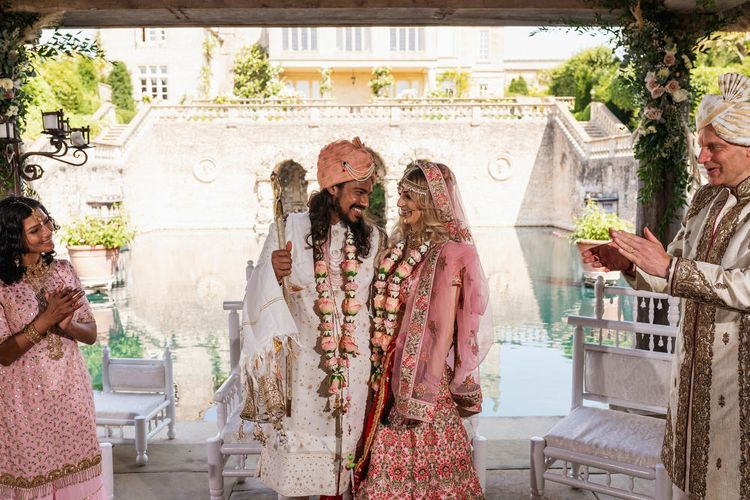 Bride and groom in pink, white and gold Indian wedding outfits at Hindu wedding ceremony