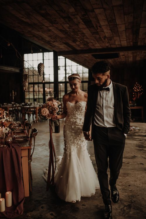 Bride in Emma Beaumont wedding dress and groom in tuxedo walking through their intimate reception at Hidden Cabin Barns