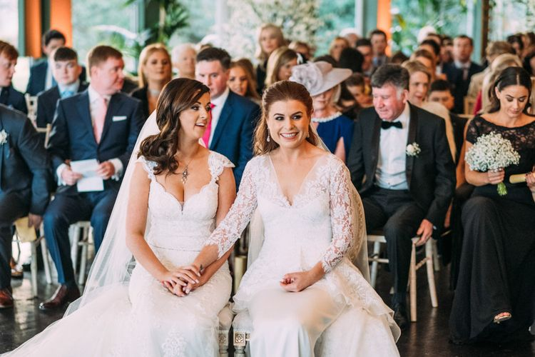 Two Brides in Lace Wedding Dresses Holding Hands at Wedding Ceremony