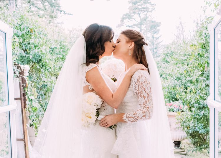 Two Brides in Lace Wedding Dresses Kissing