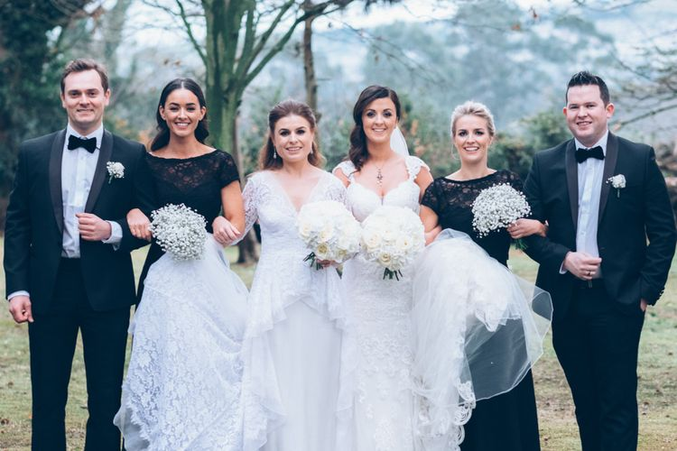Wedding Party Portrait with Black Tie Suits and Two Bride in Alice Temperley and Essense of Australia Lace Wedding Dresses