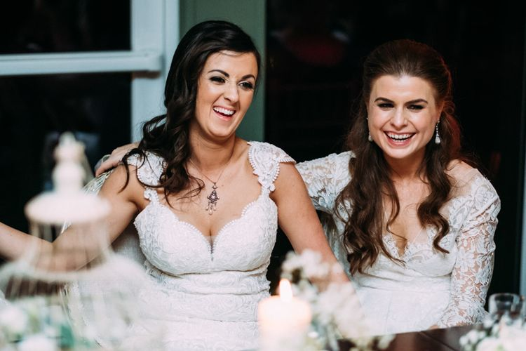 Two Bride in Lace Wedding Dresses Laughing at Wedding Reception Speeches