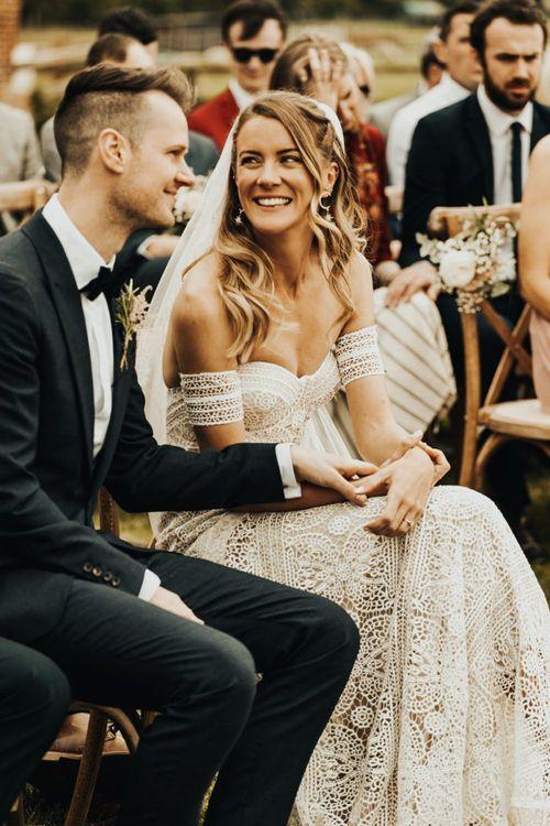 Boho Bride in Rue De Seine Wedding Dress and Groom in Black Tie Suit Holding Hands