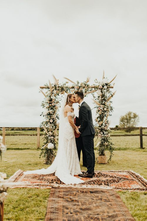 Boho Bride in Rue De Seine Wedding Dress and Groom in Black Tie Suit Kissing at the Floral Arch Altar
