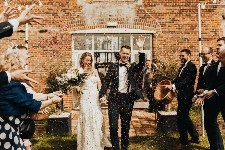 Confetti Moment with Boho Bride in Rue De Seine Wedding Dress and Groom in Black Tie Suit