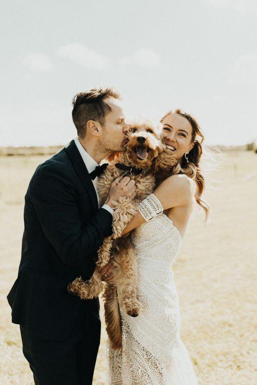 Boho Bride in Rue De Seine Wedding Dress and Groom in Black Tie Suit Hugging Their Pet Cockapoo