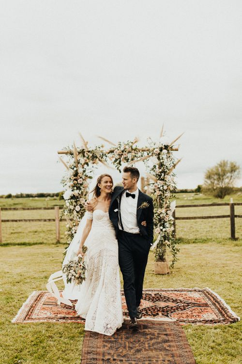 Boho Bride in Rue de Seine Wedding Dress and Groom in Black Tie Suit Embracing in Front of Their Floral Arch