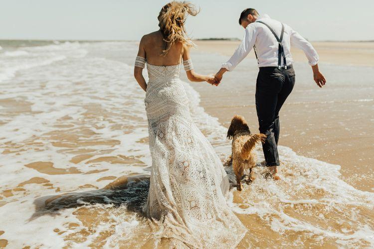 Boho Bride in Rue de Seine Wedding Dress and Groom in Black Tie Suit Walking Through The Surf with their Pet Cockapoo