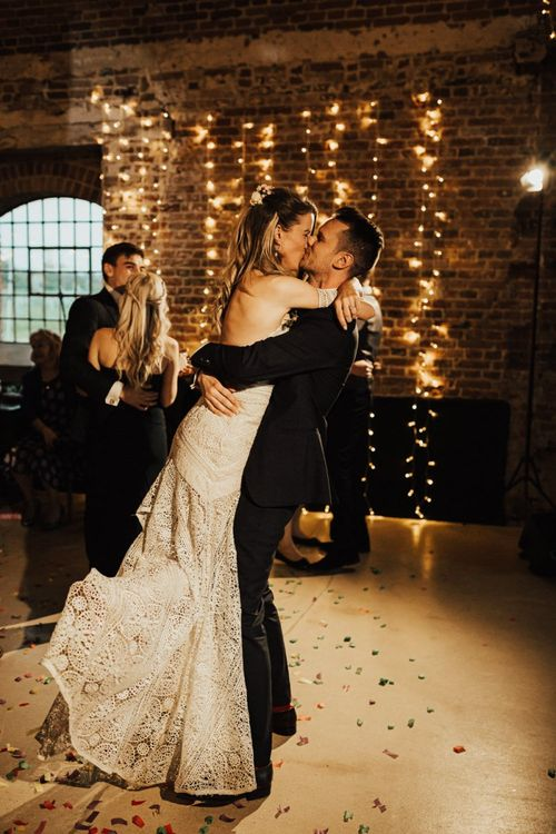 Groom Picking Up His Bride and Kissing Her on the Dance Floor